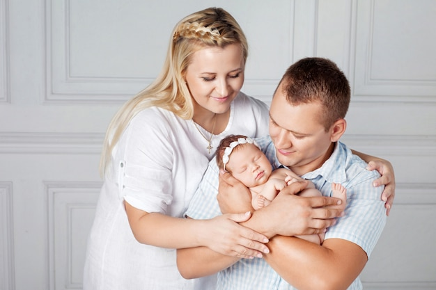Heureux parents tenant une jolie fille nouveau-née. maman, papa et bébé. portrait, sourire, famille, nouveau né, mains famille heureuse