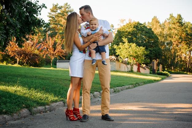 Heureux parents tenant sur les mains un petit garçon vêtu de la broderie et s'embrassant