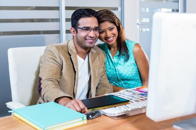 Heureux partenaires travaillant ensemble sur ordinateur