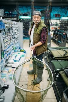 Heureux pêcheur tient un filet dans un magasin de pêche