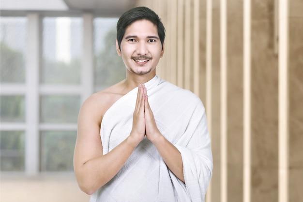 Heureux pèlerin de hadj asiatique avec le geste de la main en prière