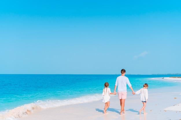 Heureux père et adorables petits enfants sur la plage tropicale en s'amusant. vacances en famille