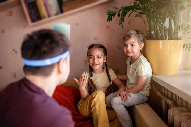 Heureux père adulte jouant au jeu de société avec ses deux enfants à l'intérieur, les valeurs familiales en fait