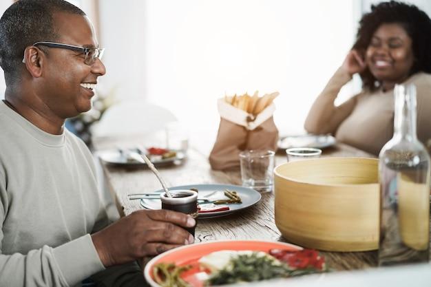 Heureux père africain boire de la yerba mate pendant le déjeuner à la maison