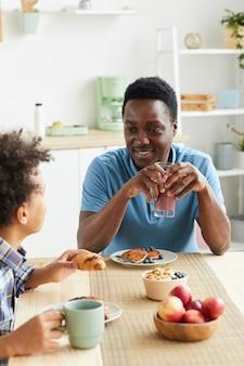Heureux père africain prenant son petit déjeuner avec son fils, ils sont assis à la table et parlent dans la cuisine