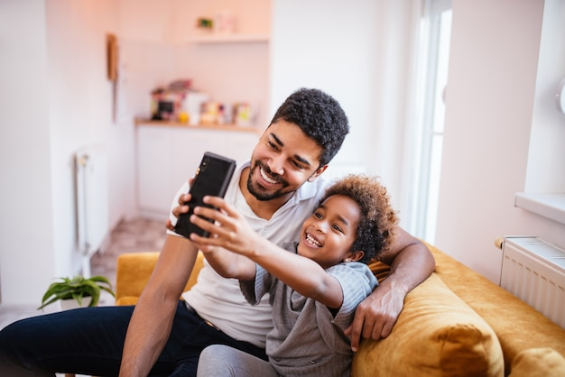 Heureux père afro-américain et fille faisant un selfie à la maison.
