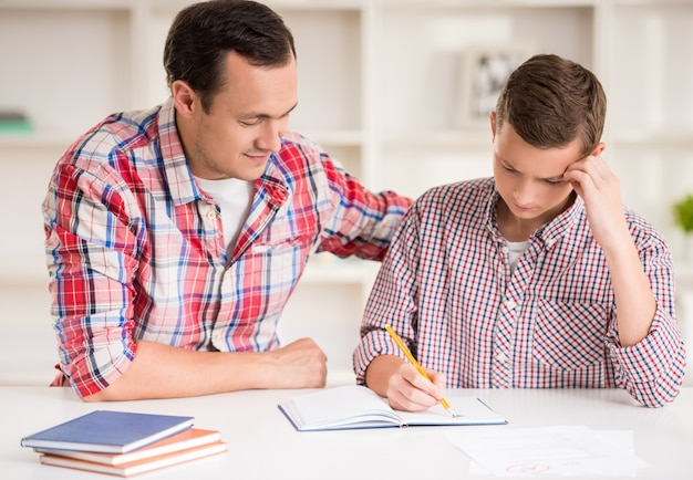 Heureux père aide son fils à faire ses devoirs.