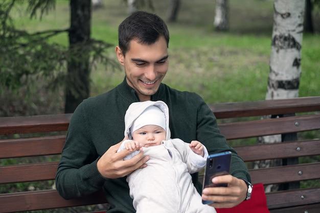Heureux père avec bébé nouveau-né assis sur un banc prenant selfie dans le parc. concept de paternité
