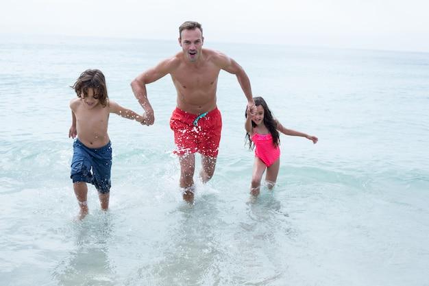 Heureux père courir avec des enfants à la plage