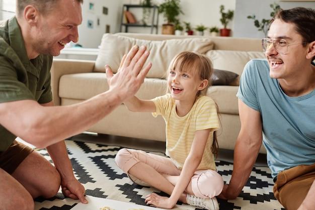 Heureux père donnant un high-five à son enfant pendant qu'ils jouent par terre dans la pièce