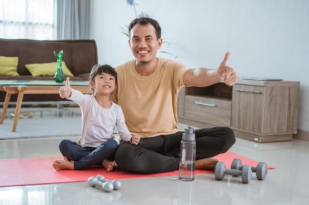 Heureux père et enfant faisant de l'exercice ensemble. portrait d'entraînement familial sain à la maison. homme et sa fille sport