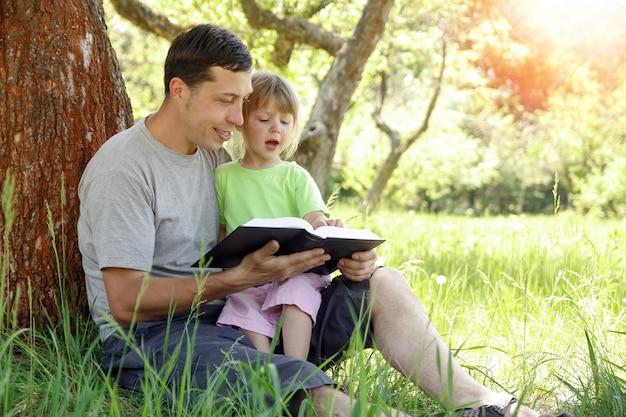 Heureux père avec un enfant lisant un livre sur la nature de la bible