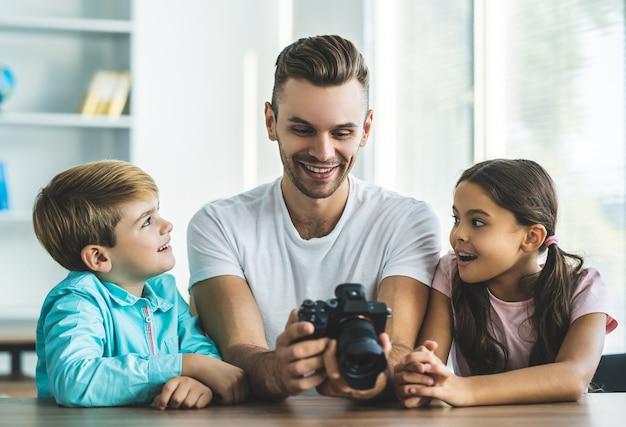 L'heureux père et enfants avec un appareil photo assis à la table