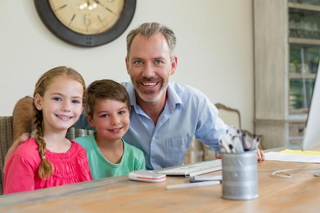 Heureux père et enfants assis au bureau