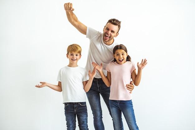 L'heureux père et enfants faisant des gestes sur fond blanc
