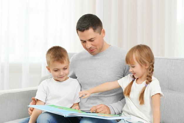 Heureux père et enfants lisant un livre sur le canapé