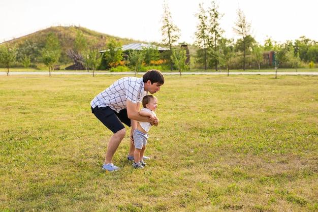 Heureux père de famille et enfant sur le pré en été sur la nature.