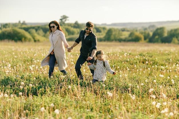 Heureux père de famille, mère et fille enfant sur la nature au coucher du soleil.