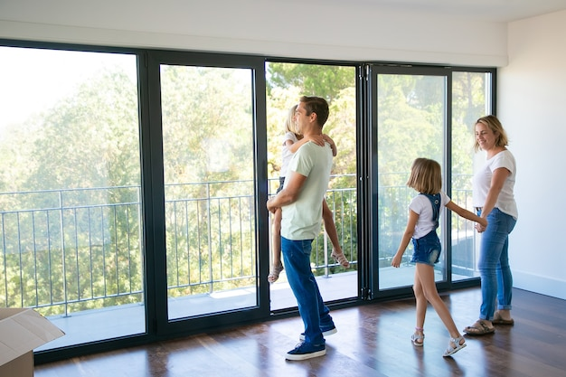 Heureux père avec fille debout près d'un balcon ouvert et souriant