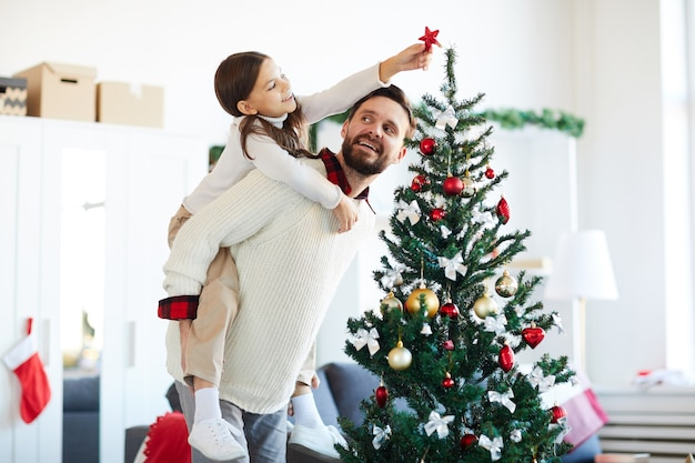 Heureux père et fille décorant le sapin de noël