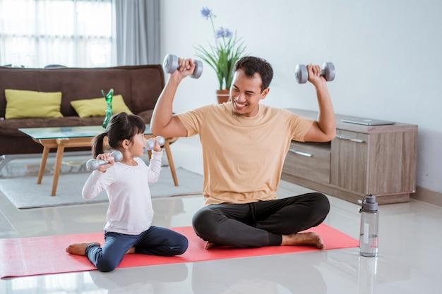 Heureux père et fille exerçant faisant des haltères soulever ensemble dans le salon