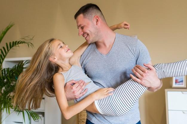 Heureux père et fille jouant à l'intérieur