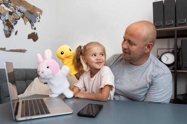 Heureux père et fille jouant avec des marionnettes