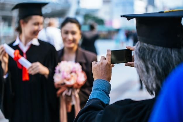 Heureux père et fille en robes de graduation faisant selfie.