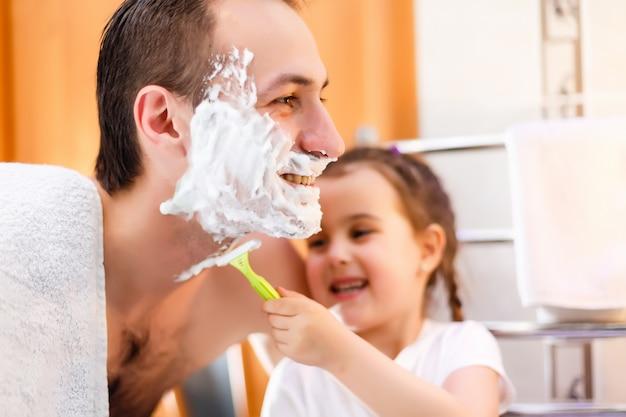 Heureux père et fille s'amusant avec de la mousse à raser dans la salle de bain