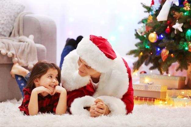Heureux père et fille sur le sol dans la salle de noël décorée