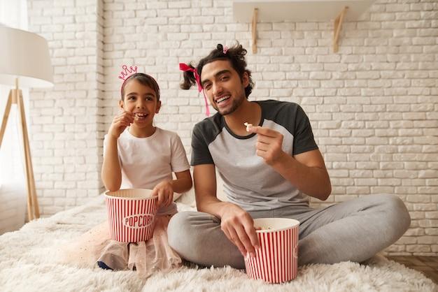 Heureux père et fille sont assis sur un canapé