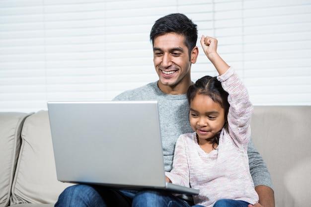 Heureux père et fille utilisant un ordinateur portable sur le canapé
