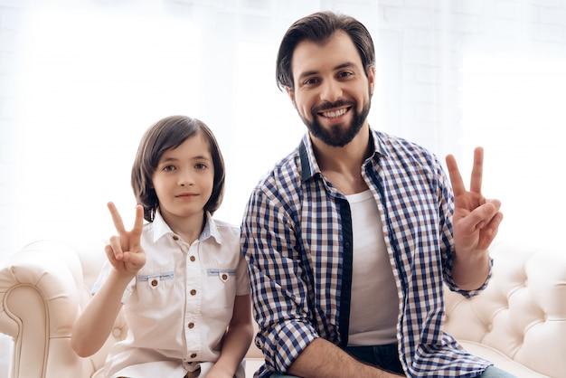 Heureux père et fils adolescent montrant le signe de la victoire.