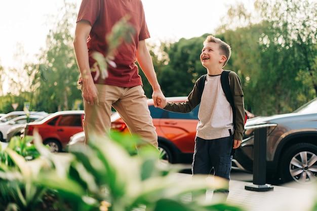 Heureux père et fils allant aux cours, le parent emmène son enfant à l'école dans un élève de première année de