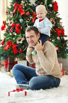 Heureux père et fils à l'arbre de noël dans le salon
