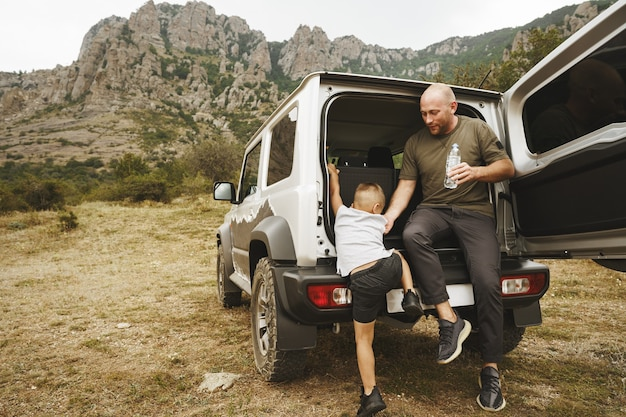 Heureux père et fils assis dans le coffre de la voiture