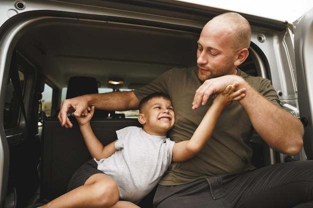 Heureux Père Et Fils Assis Dans Le Coffre De La Voiture Photo Premium