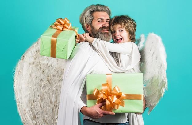 Heureux père et fils en costume d'ange avec boîte-cadeau