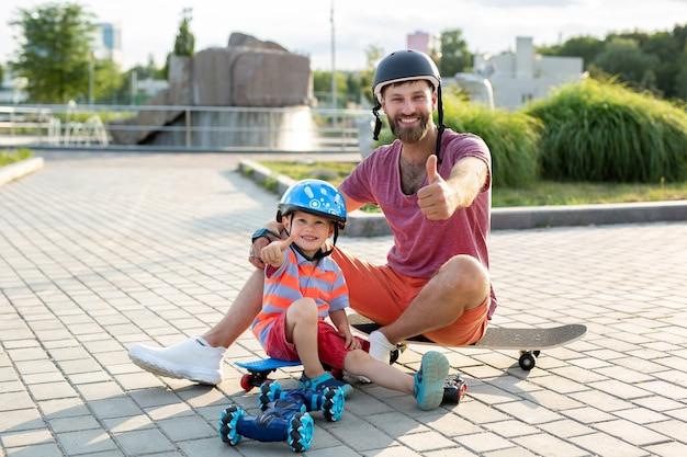 Heureux père et fils dans des casques jouent dans le parc avec une voiture robot contrôlée par un gant assis sur des planches à roulettes.
