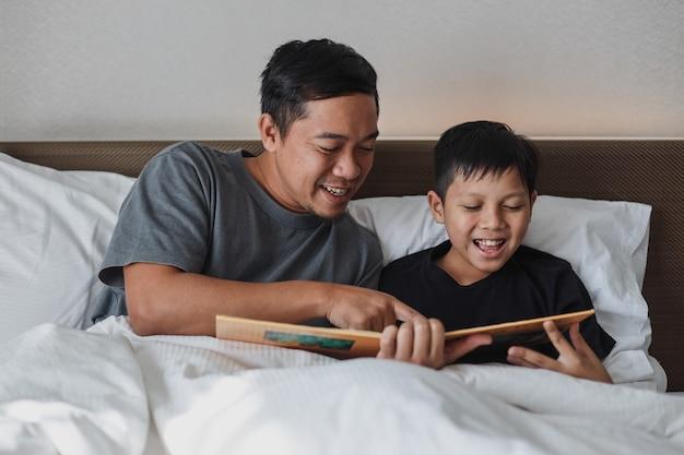 Heureux père et fils lisant un livre ensemble sur le lit