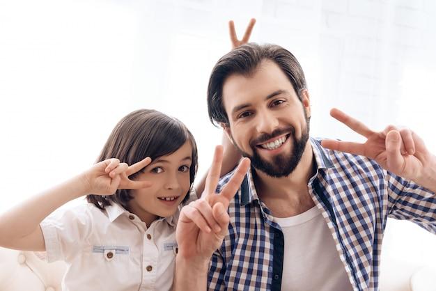Heureux père avec fils montre des signes de victoire.