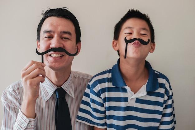 Heureux père et fils s'amusant avec une fausse moustache