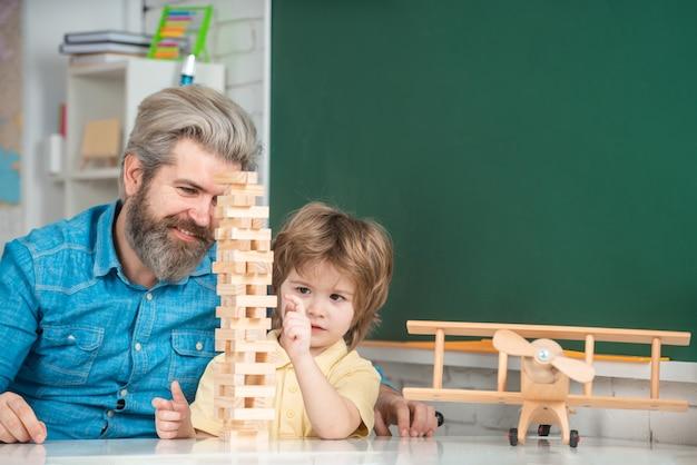 Heureux père et fils à la table jouant à des jeux de société concept d'apprentissage et d'éducation
