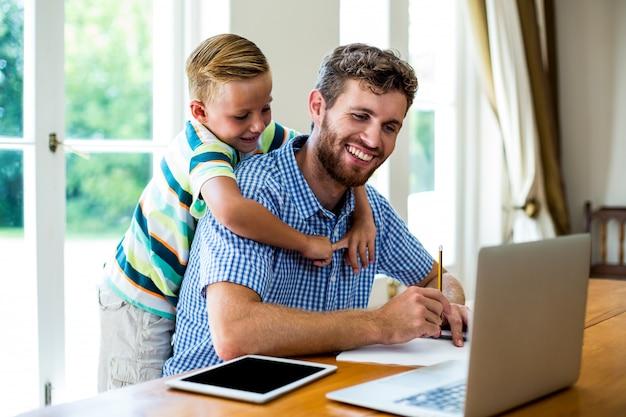 Heureux père avec fils travaillant par technologies à table