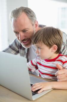 Heureux père et fils utilisant un ordinateur portable