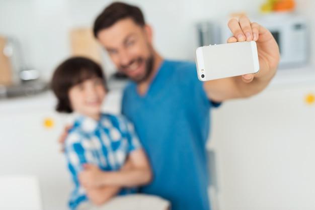 Heureux père et fils utilisant un smartphone à la maison.