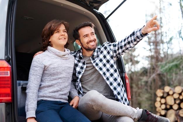 Heureux père et fils voyageant en voiture