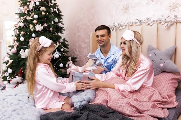 Heureux père de mère de famille et enfants le matin de noël au lit en pyjama