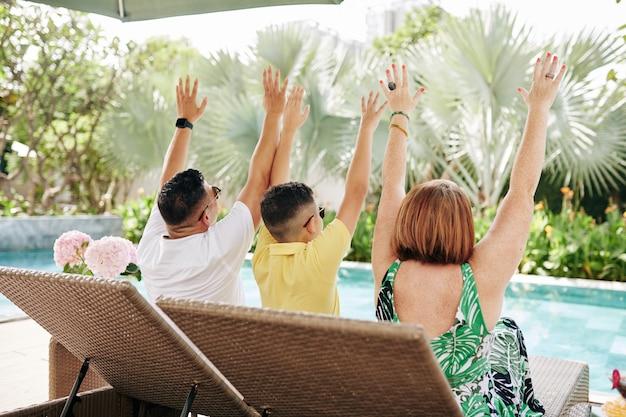 Heureux père, mère et fils assis sur une chaise longue au bord de la piscine et levant la main pour célébrer de bonnes vacances
