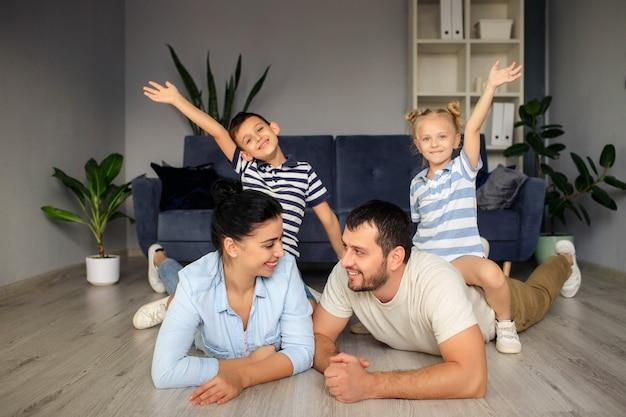 Heureux père et mère avec de petits enfants assis sur le sol près du canapé et riant tout en s'amusant ensemble à la maison pendant le week-end